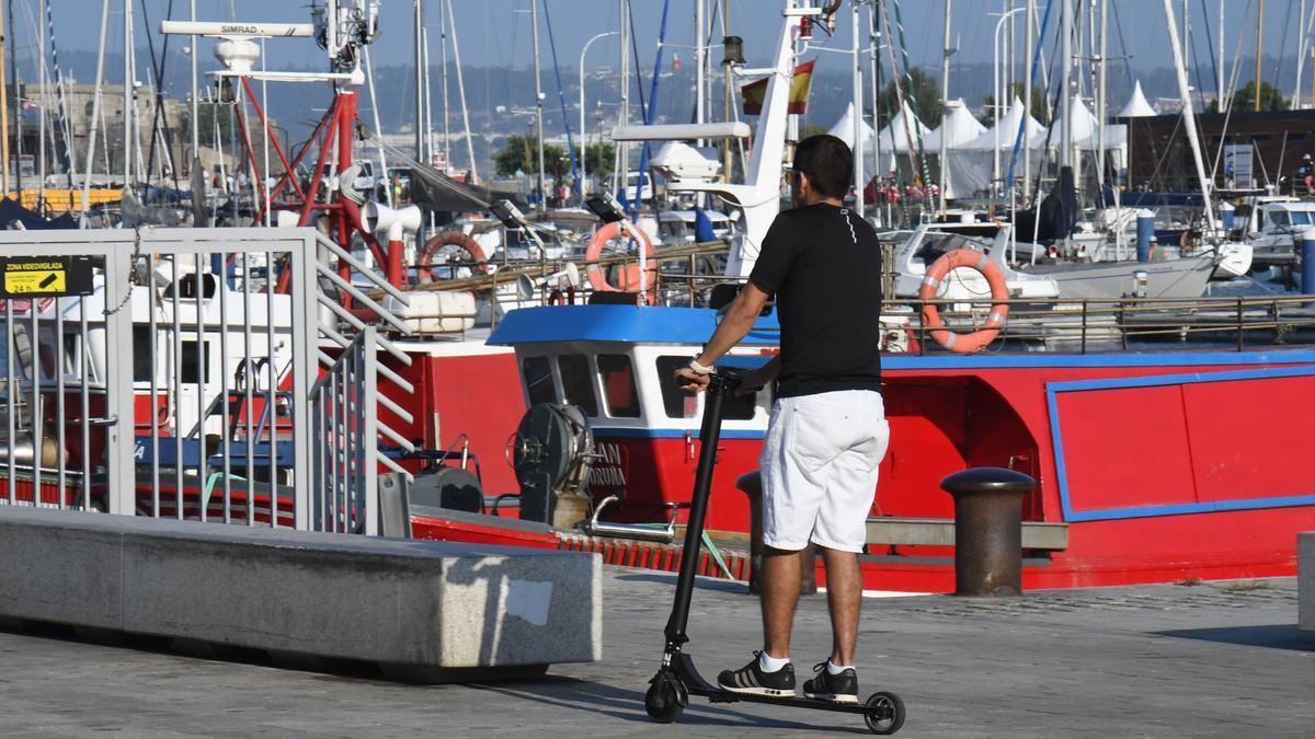 Una persona circula en patinete por la Marina en A Coruña.