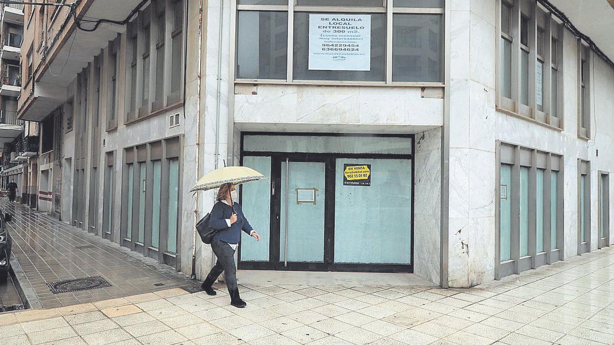 Una mujer pasa frente a una sucursal cerrada en el Grau de Castelló.