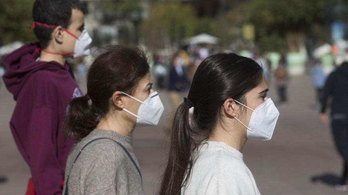 Tres jóvenes pasean en Valencia con mascarilla.