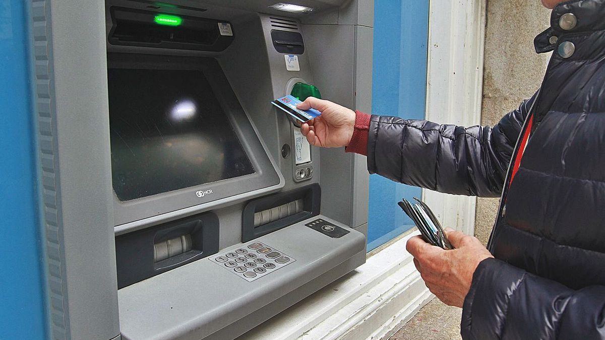 Un hombre introduce su tarjeta bancaria en un cajero automático de Abanca.     // IÑAKI OSORIO