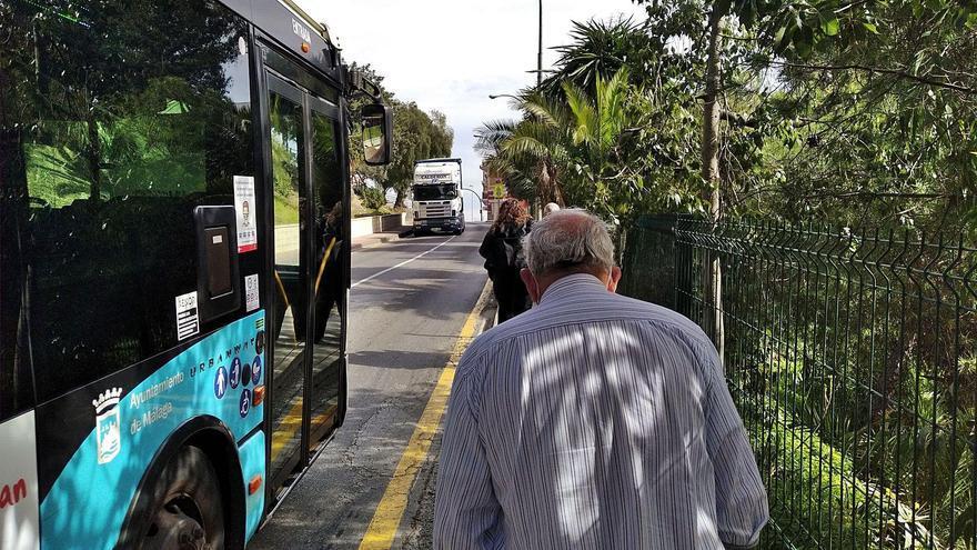 El autobús pasa junto a los peatones, que  avanzan en fila india por este peligroso tramo de Los Prados.