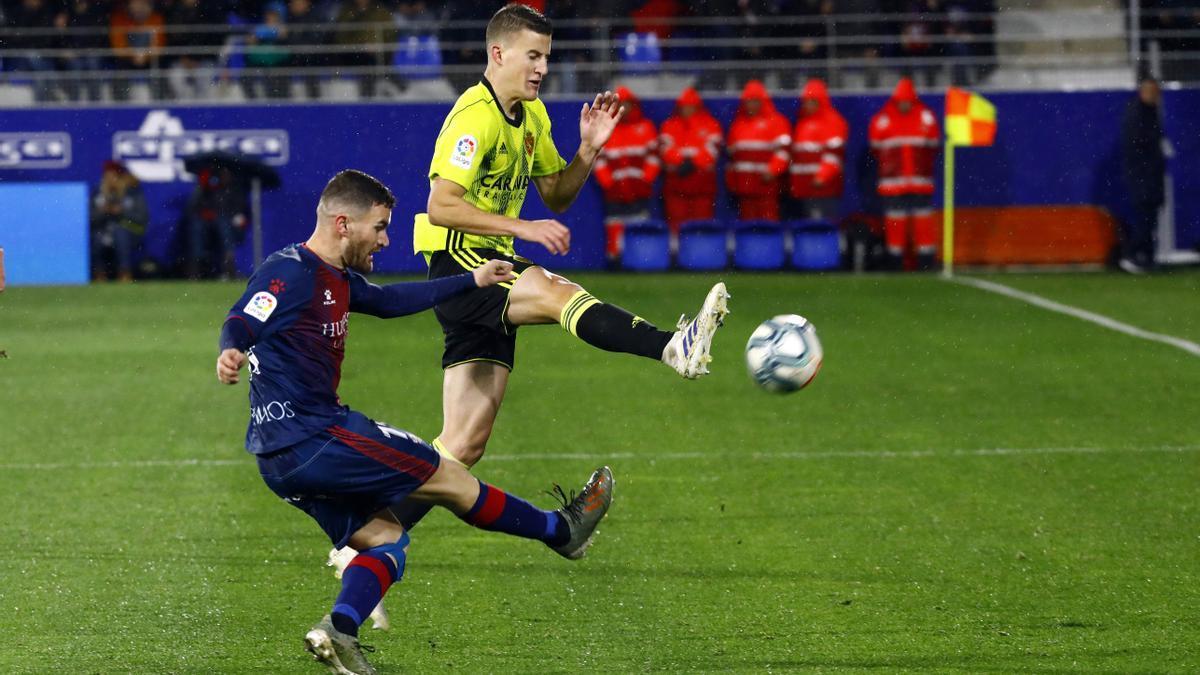 Nieto trata de esquivar el despeje del jugador del Huesca Galán en El Alcoraz.