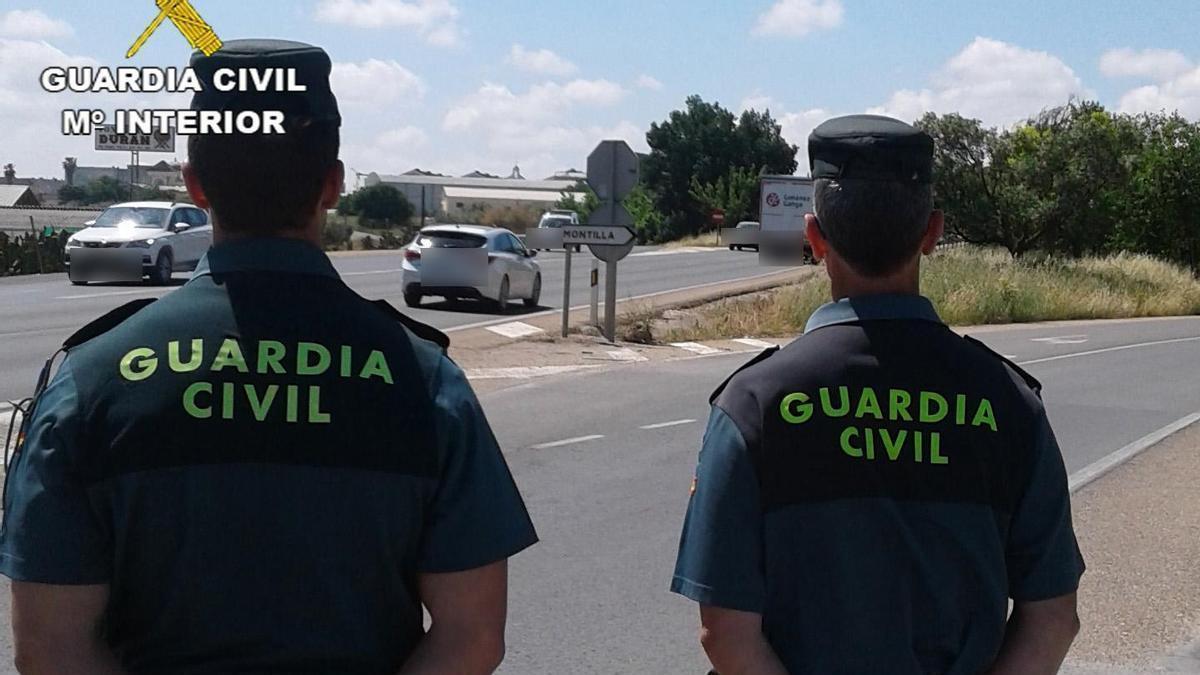 Dos guardias civiles vigilan una de las entradas a Montilla.