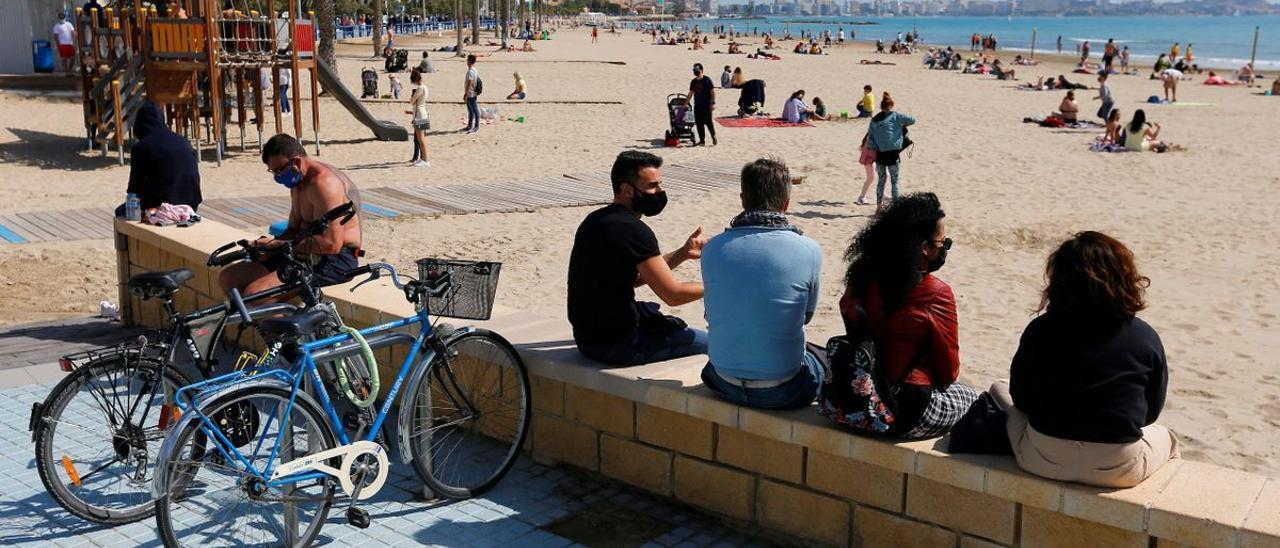 Personas con mascarillas en la playa del Postiguet de Alicante.