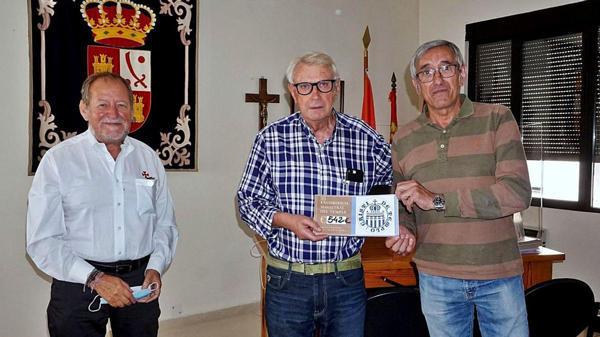 José Luis Campos Santiago (derecha) entrega a Jesús Lorenzo Más (centro) el cheque para la cofradía.   Cedida
