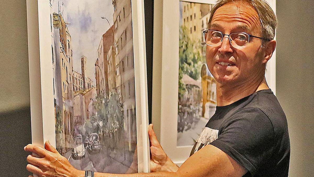 Joan Carrió, coordinador de l'exposició del Cercle, mostra alguns dels quadres exposats   JORDI BIEL