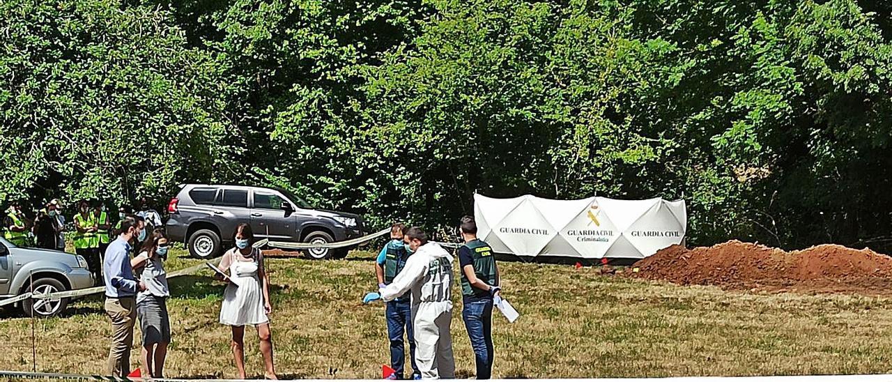 Funcionarios judiciales y agentes de la Guardia Civil, en la zona de El Rellán (Grado) donde hallaron decenas de casquillos de bala y cerca del lugar en el que se encontraron tres cadáveres. | S. A.
