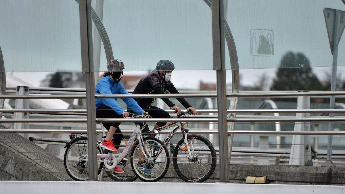 Ciclistas con mascarilla en el puente de As Correntes.