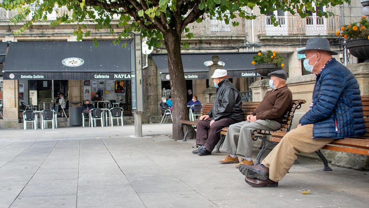 Tres personas mayores observan una cafetería abierta en un Carballiño confinado.