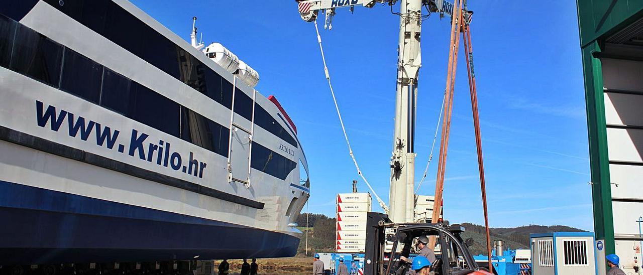 Operativo con grúas para la botadura de un catamarán, en Castropol, en 2018. Abajo,  la zona del muelle sur donde Gondán propone crear una rampa. | T. Cascudo