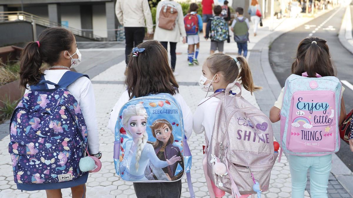 Varias niñas con sus carteras del colegio.