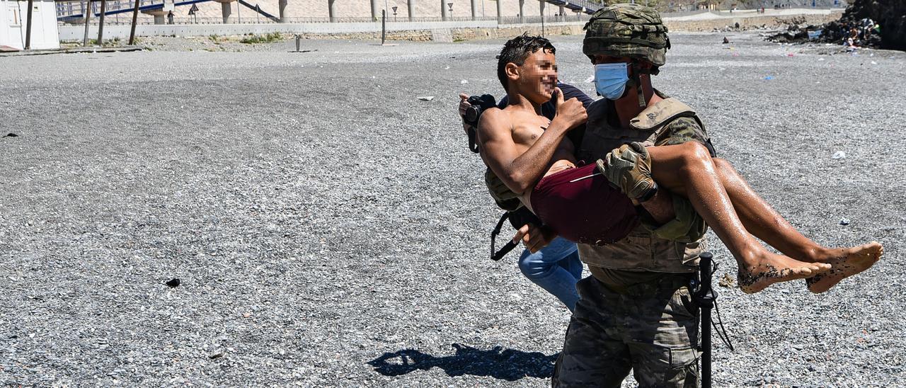 Un militar traslada a un menor rescatado en Ceuta