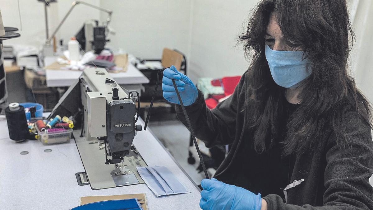 Una operaria cose la goma a una mascarilla en el taller de la empresa de moda Ángel Iglesias. | Nico Rodríguez