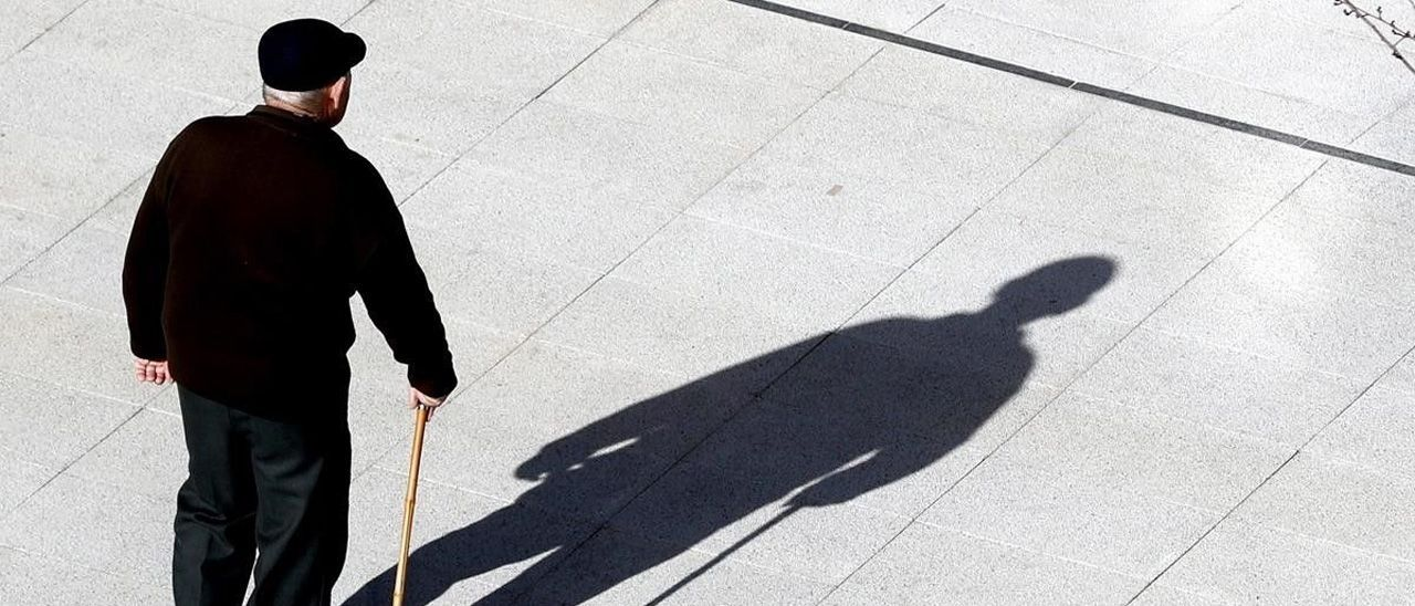 Un jubilado camina en Bilbao por una plaza pública.