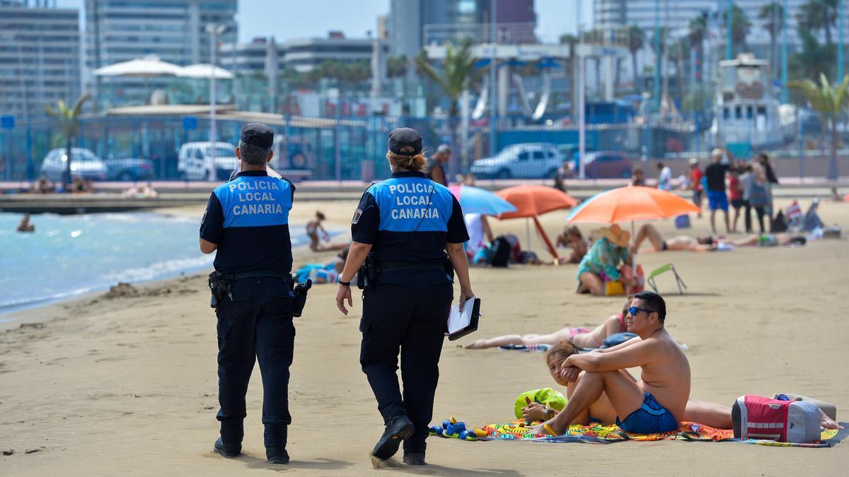 Dos agentes pasean en una playa de Las Palmas de Gran Canaria