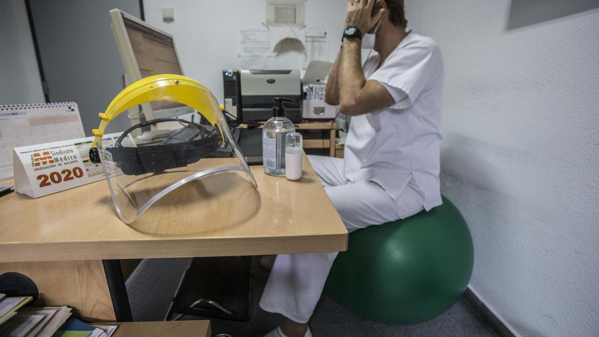 Un médico pasa consulta en una pelota de pilates debido a que su silla se rompió hace meses y no se la reponen.