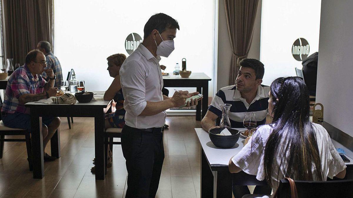 Bruno Gomes atiende a dos de sus clientes en el Restaurante Miradouro.