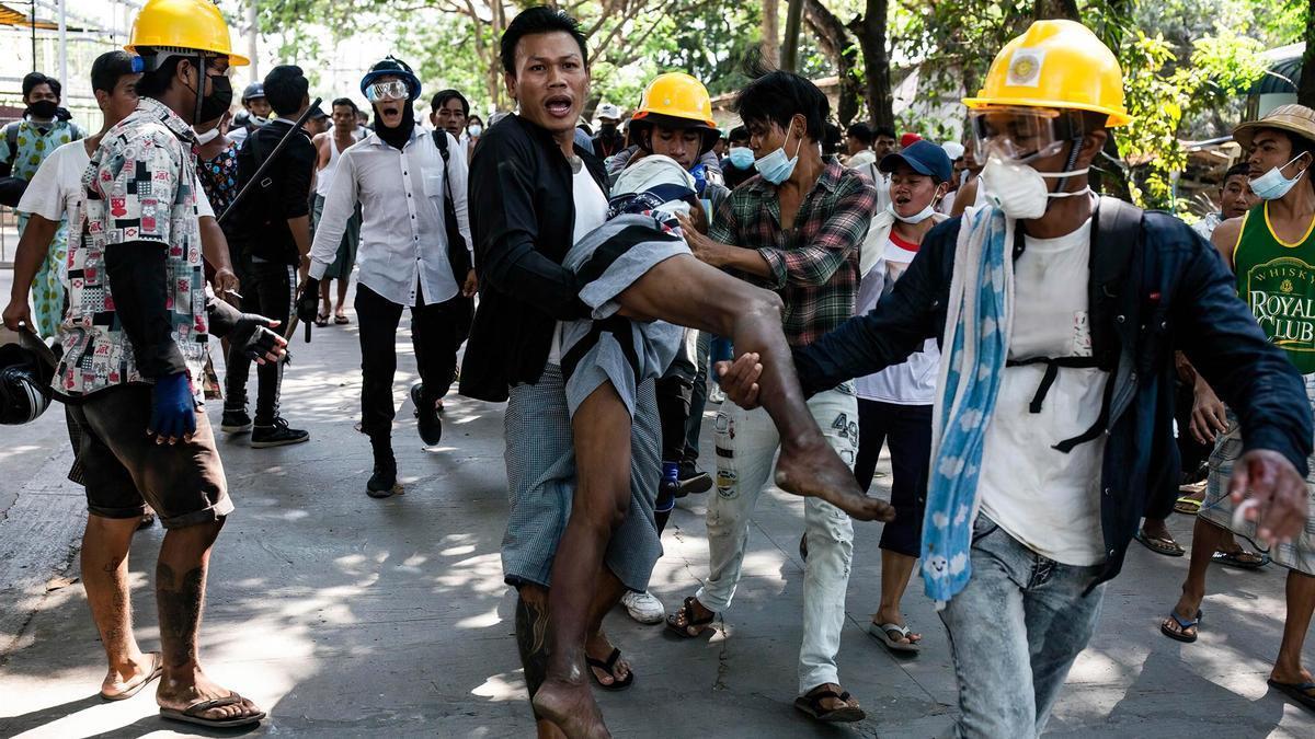 Manifestantes cargan a un hombre herido durante una jornada de protestas en Rangún.