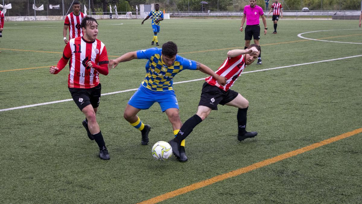 Dos jugadores del Racing Rafelcofer intentan robar un balón a otro del Denia UD