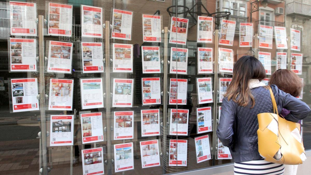 Dos mujeres miran las ofertas colgadas en el escaparate de una agencia inmobiliaria.