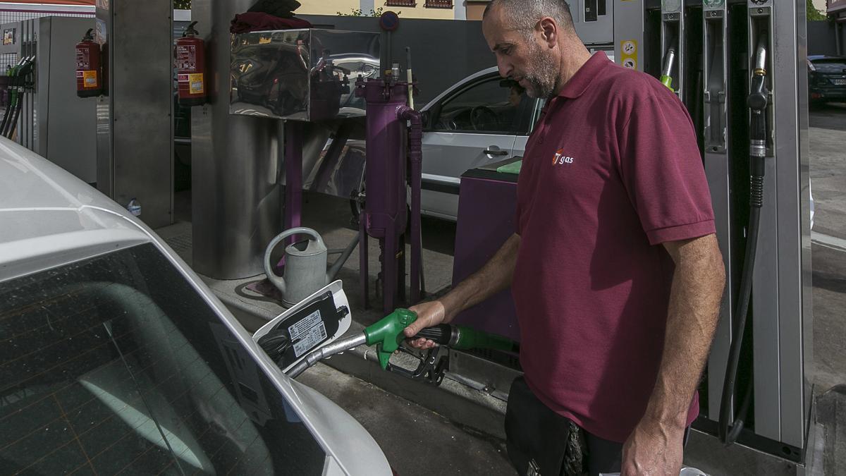 Empleado reposta un vehículo en una gasolinera