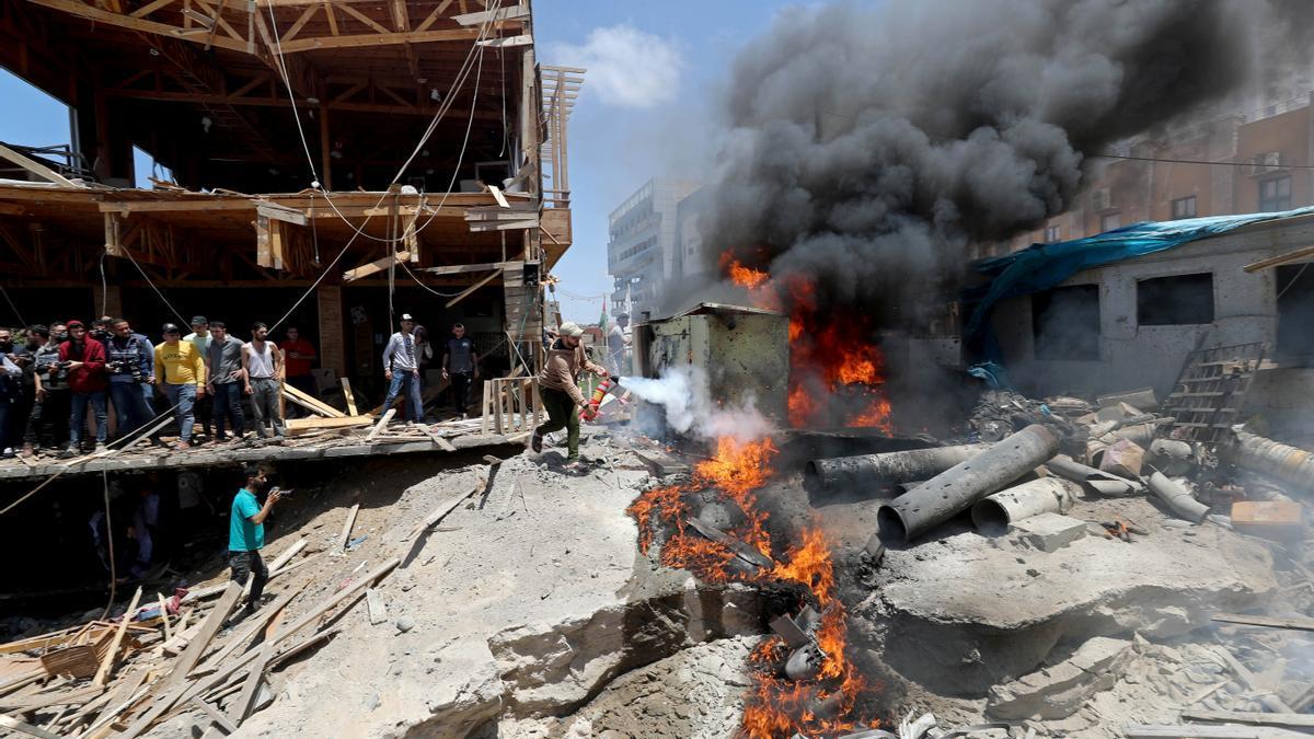 Un palestí apaga un incendi provocat per un atac aeri a Gaza