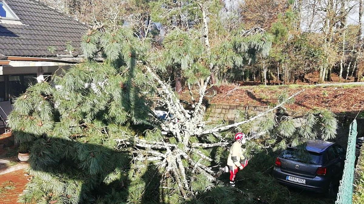 Una persona corta un árbol que se cayó sobre una casa a causa del temporal en Redondela.     //  M. VÁZQUEZ