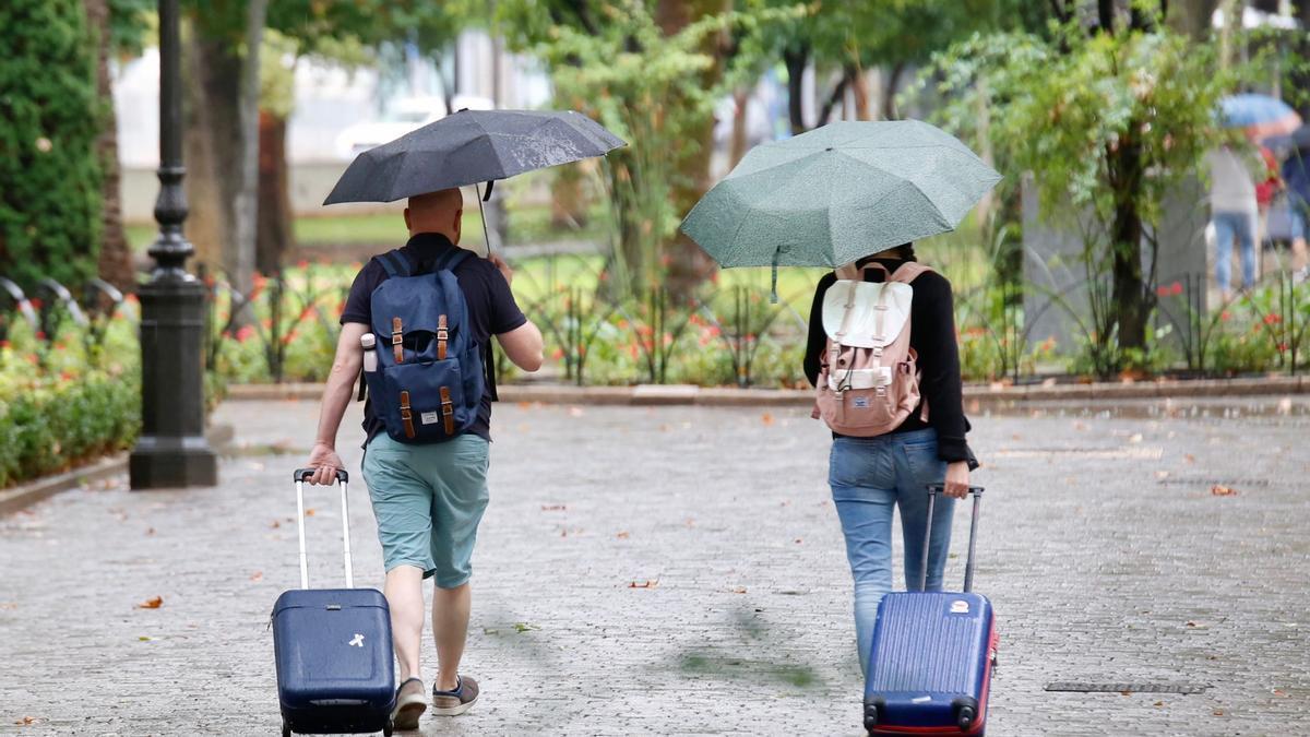 Dos personas se protegen con paraguas en los jardines de la Agricultura en Córdoba.