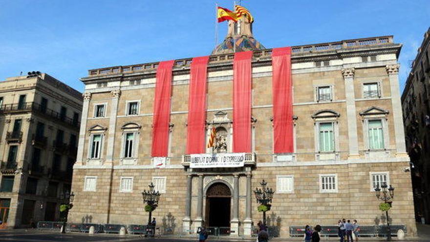 La façana de la Generalitat llueix quatre franges vermelles gegants per commemorar l'1-O