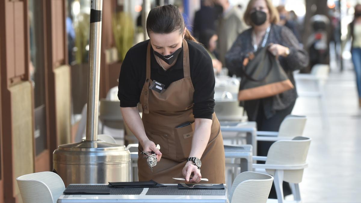 Una camarera preparando las mesas de una terraza.