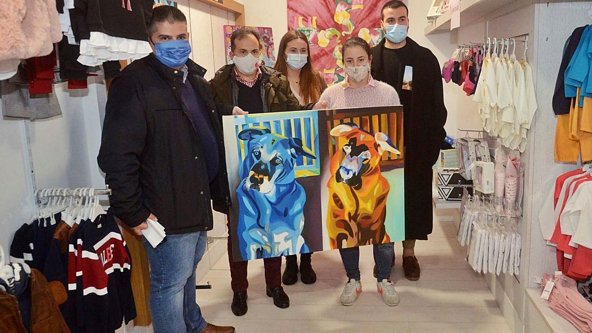 Los participantes en la presentación muestran dos de las obras expuestas en una tienda. |  // NOÉ PARGA