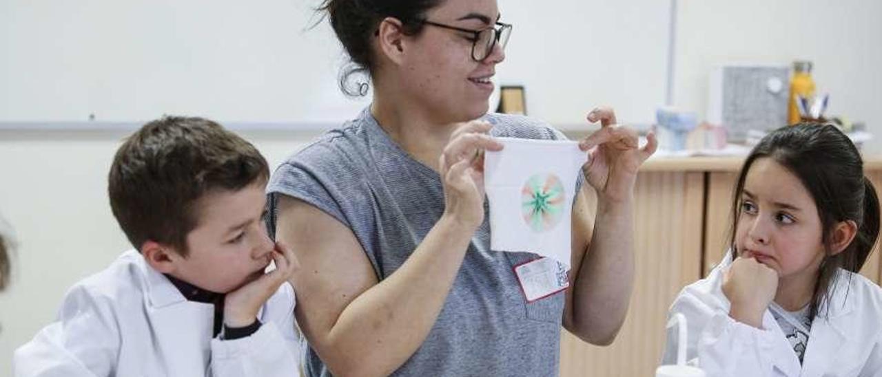 Isabel Blanco explica a los niños cómo realizar un dibujo sobre tela.
