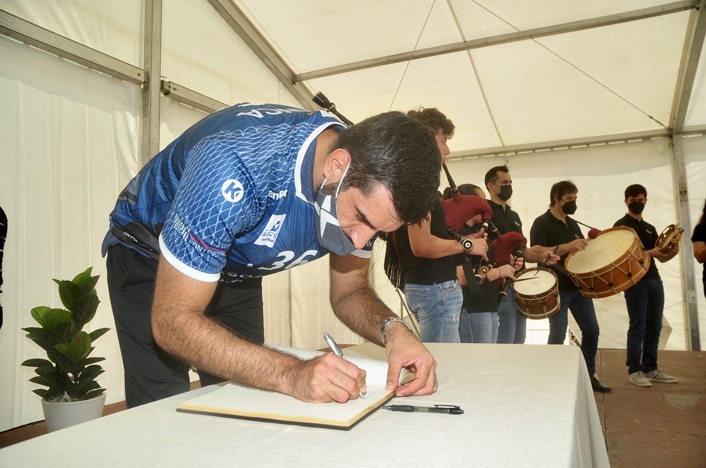 Corrales firma en el libro del Concello, con el grupo Tromentelo al fondo. Rafa Vázquez.jpg