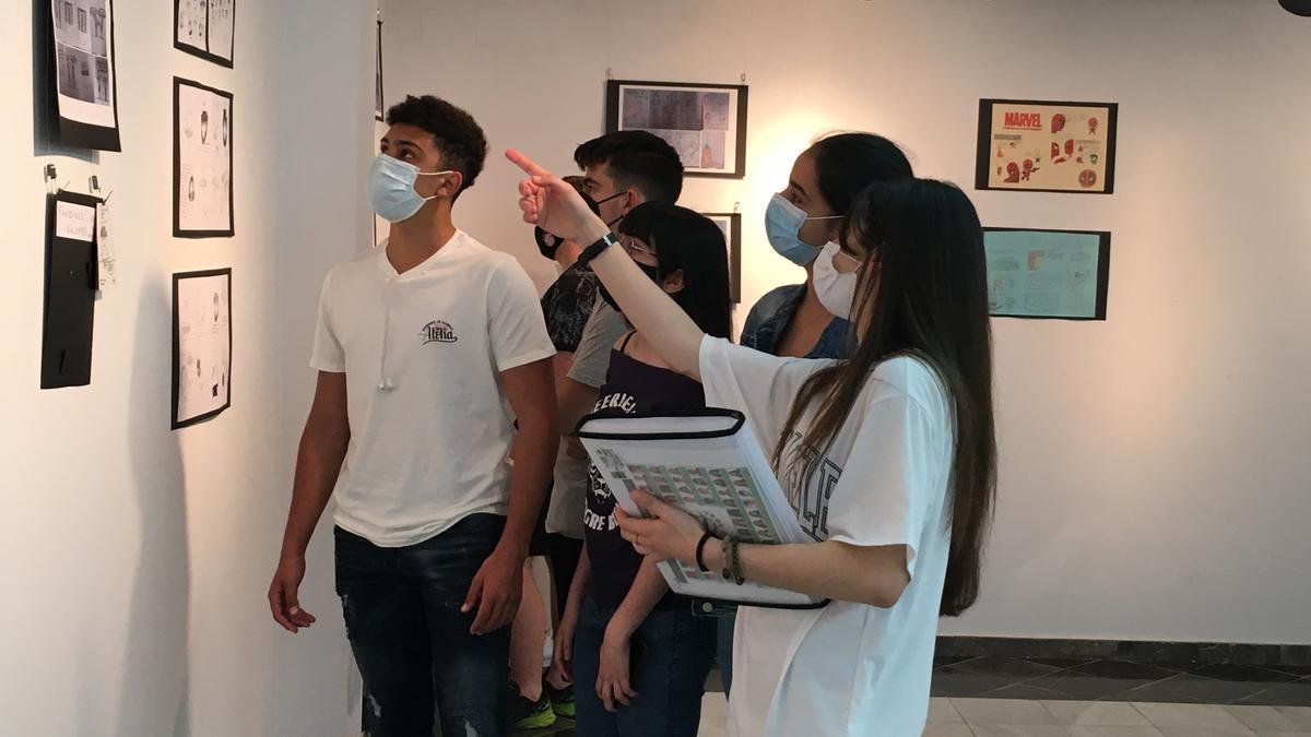 Los estudiantes del IES Río Arba contemplan sus viñetas en la exposición en la Casa de Comercio de Tauste.