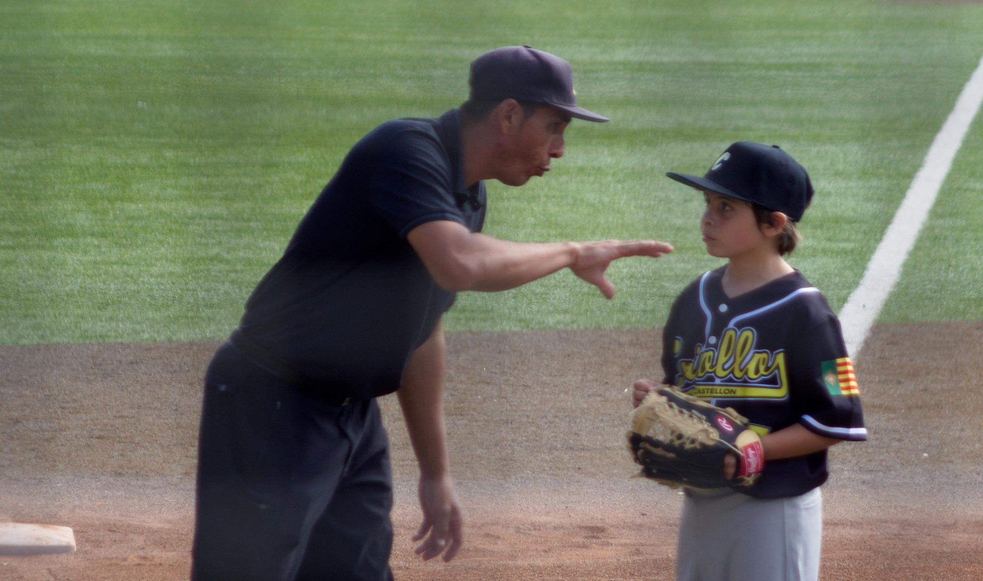 El entrenador da instrucciones a uno de los niños de los Criollos.