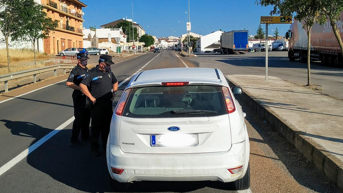 La policía local informa a un conductor sobre el cierre del municipio