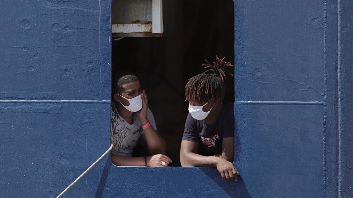 Unos migrantes aguardando para desembarcar al recibir el permiso para atracar en el puerto siciliano de Augusta tras una semana de espera en el mar