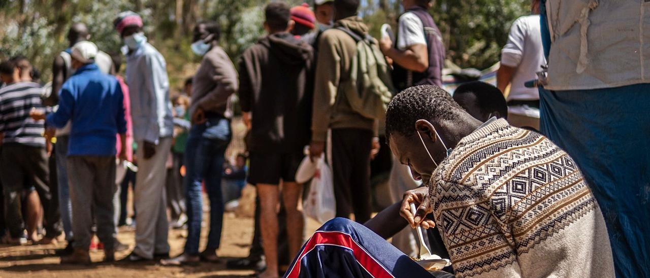 Migrantes hacen cola en el campamento de Las Raíces para romper el ayuno del Ramadán. | | ANDRÉS GUTIÉRREZ