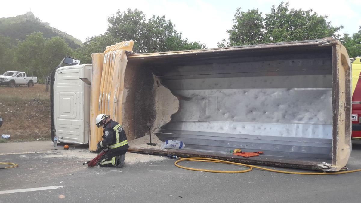 Un bombero junto al camión volcado entre Felanitx y Portocolom.