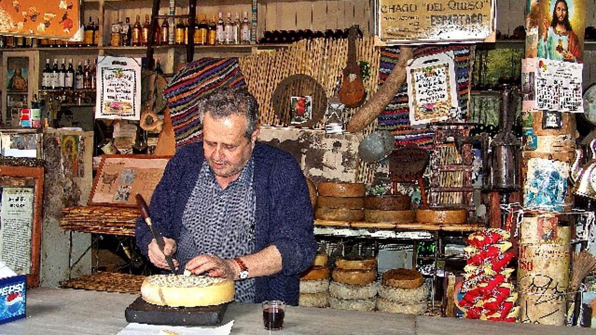 Santiago Gil Romero, en una típica estampa cortando queso en su bodega de Guía, con la copa de vino al lado y sus numerosos recuerdos como decoración.