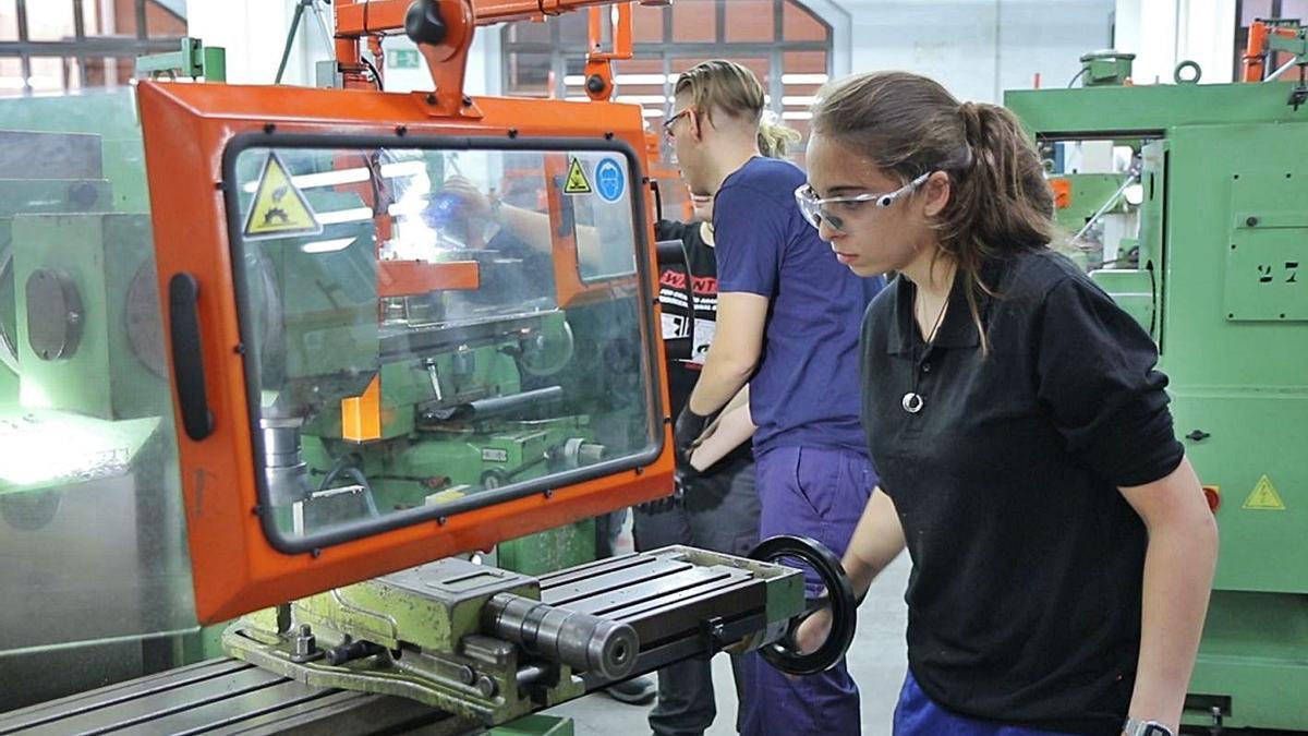 Una estudiante maneja  maquinaria en un taller de FP.  levante-emv