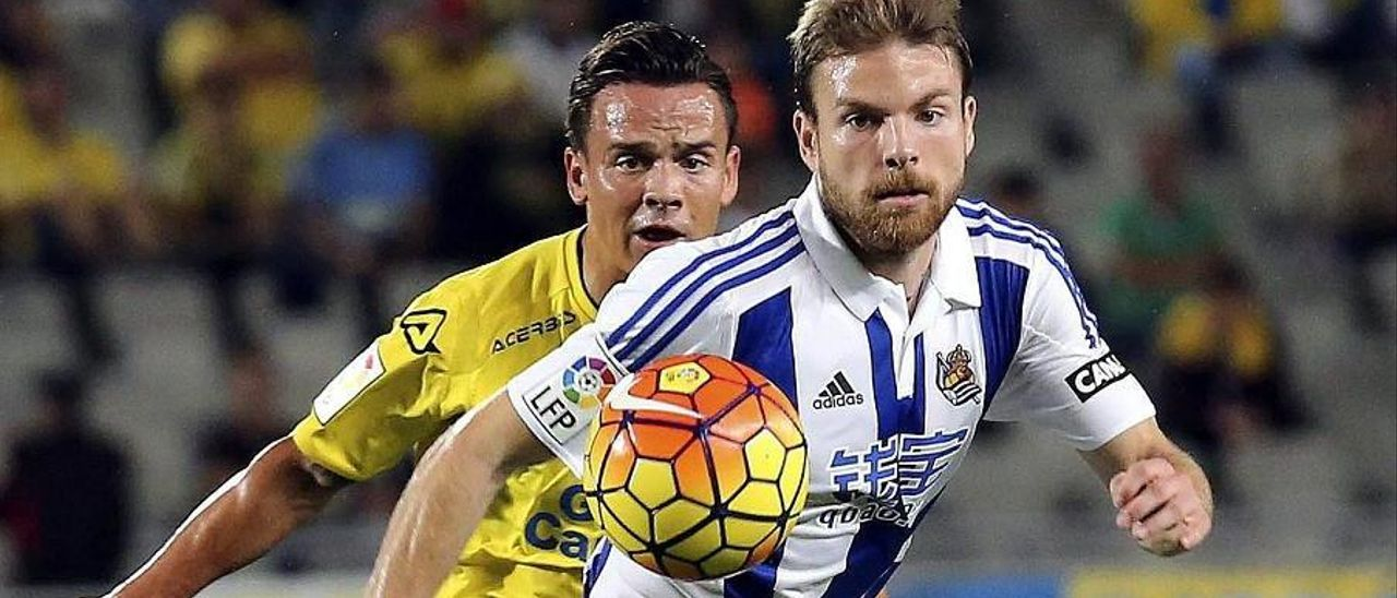 Roque Mesa presiona al jugador de la Real Asier Illarramendi.