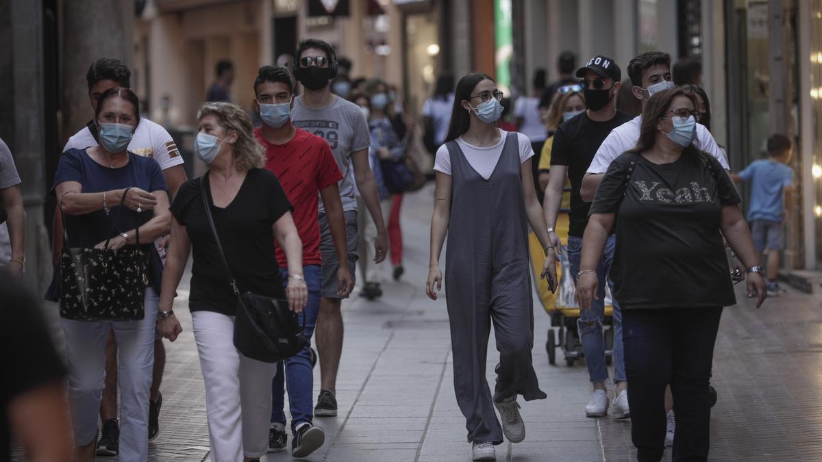 Ciudadanos caminan por Palma con mascarilla