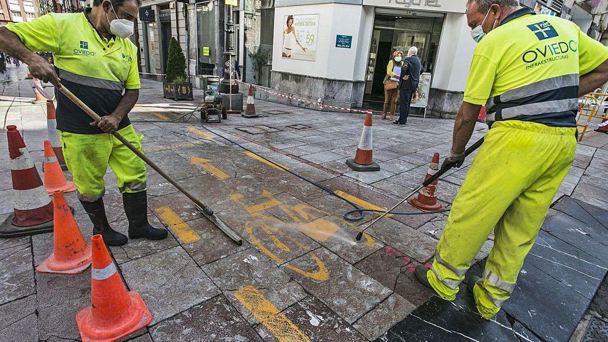 Operarios borrando la pintura del carril bici en la calle Doctor Casal.