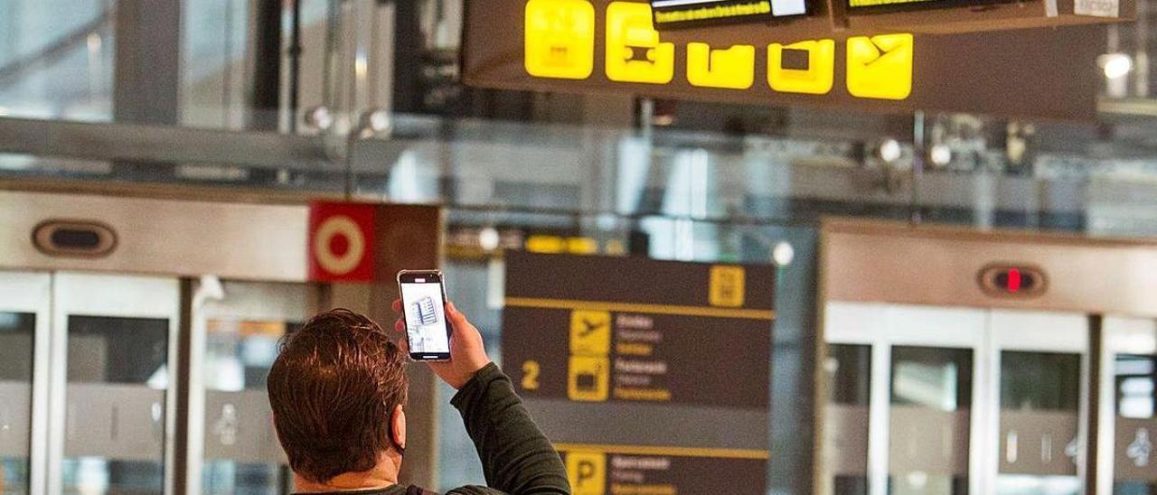 Un viajero fotografía con su móvil la pantalla de vuelos del aeropuerto
