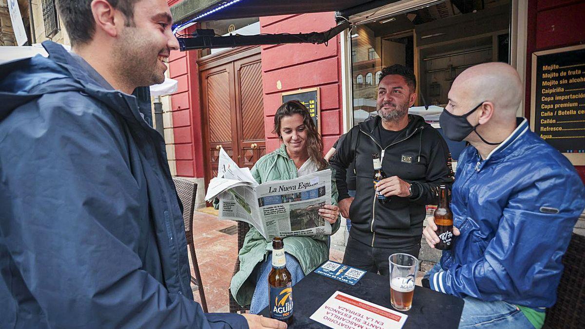 Por la derecha, Manuel Colla, Juan Carlos Álvarez, Natalia Cruz –leyendo LA NUEVA ESPAÑA, diario del mismo grupo de comunicación que este medio– y Santi Rodríguez, en una terraza de Oviedo.