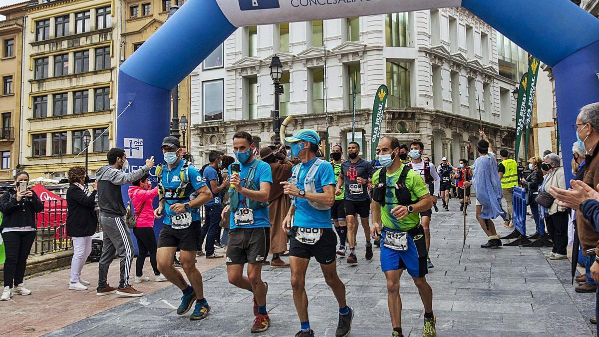 Arriba, la llegada del pelotón a Oviedo. A la izquierda, un grupo de corredores posa ante la Catedral de Oviedo. | Nazaret Quintas