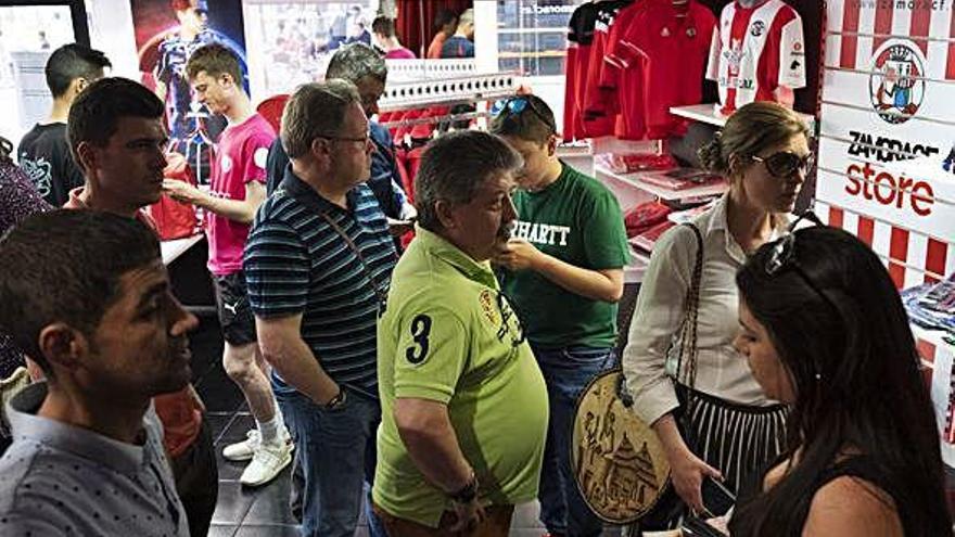 Varias personas esperan turno para retirar su entrada en el interior de la nueva tienda del Zamora CF.