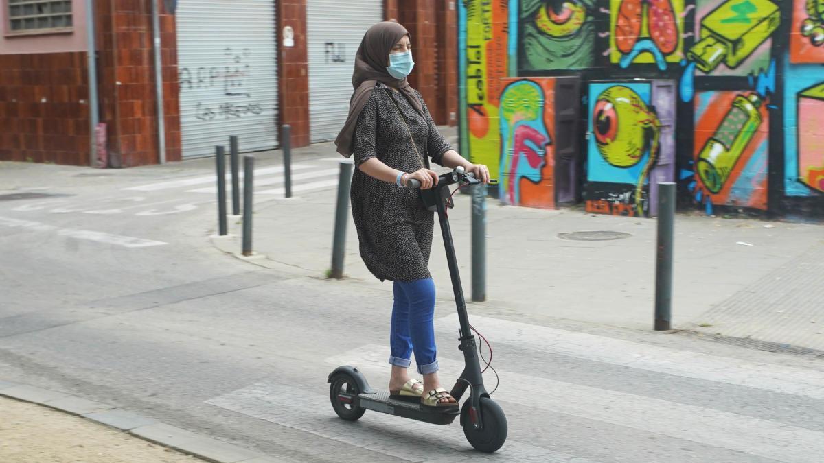 Una dona anant amb patinet elèctric per Girona