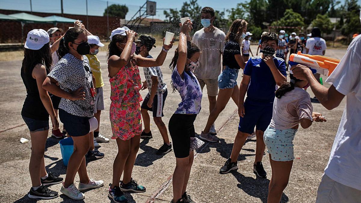 Jóvenes del Campamento Doney juegan con pistolas y vasos de agua.